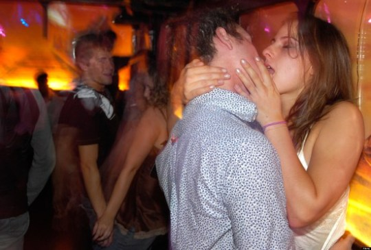Young couple kissing passionately in a nightclub
